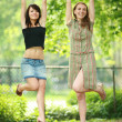 Beautiful girls hanging on tree branch — Stock Photo