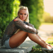 Blonde girl sitting on a green street — Stock Photo
