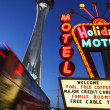 Neon motel sign and Stratosphere hotel and casino tower — Stock Photo