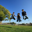 Three young friends jumping — Stock Photo