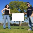 Couple holding a blank white billboard  — Стоковая фотография