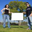 Couple holding a blank white billboard — Stock Photo #32909647