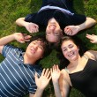 Three happy friends lying on green grass — Stock Photo