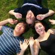 Stock Photo: Three happy friends lying on green grass