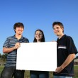 Three young friends holding a blank white billboard — Stock Photo #32909759