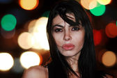 Beautiful young brunette woman at night — Stock Photo