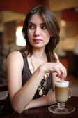 Woman enjoying latte coffee in cafe. — Stock Photo