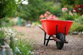 Wheelbarrow in a blooming garden — Stock Photo
