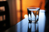 Glass of water reflects in glass table — Stock Photo