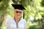 Happy senior woman in graduate cap — Stock Photo