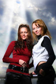 Two girlfriends, sky with rays of light — Stock Photo