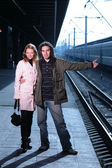 Young couple hitchhiking at train station — Stockfoto