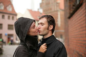 Couple kissing in an old european town square. — Stock Photo