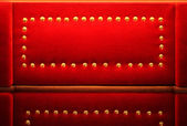 Red velvet with golden rivets retro background — Stock Photo