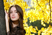 Young woman leaning to tree trunk — Stock Photo