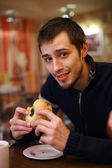 Young man eating burger — Stock Photo