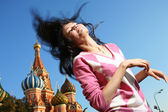 Girl in euphoria waves her long hair over blue sky at Red Square — Stock Photo