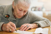 Senior lady writing — Stock Photo
