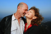 Happy mature couple embracing ontop of a city. — Stock Photo