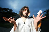 Jesus raising hands with a blank business card. — Stockfoto