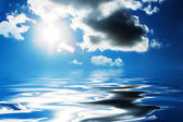 Clouds and sun reflecting in the water. — Stock Photo