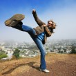 Stock Photo: Womdoing high kick ontop of Kite Hill