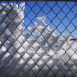 Snowy fence, blue sky behind. — Stock Photo