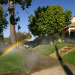 Rainbow in a sprinkler fountain — Stock Photo