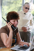 Woman talking on the phone, her mother listening behind. — Stock Photo