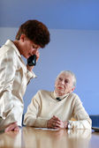 Elderly woman on appointment with social worker — Stock Photo