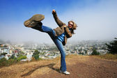Woman doing high kick ontop of the Kite Hill — Stock Photo