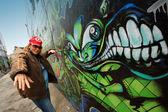 Ung kvinna rappa intill en graffiti vägg. — Stockfoto
