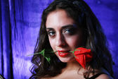 Brunette with red rose in her mouth — Stock Photo