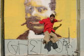 Man in red shirt jumps in front of a graffiti wall — Stock Photo