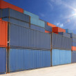 Stack of cargo containers at container yard with sunbeam — Stock Photo