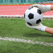 Goalkeeper's hands catching soccer ball — Stock Photo