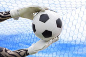 Goalkeeper's hands catching the soccer ball — Stock Photo