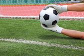 Goalkeeper's hands catching soccer ball — Stock Photo
