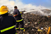 Firefighter spraying water on the waste pile after the fire. — Stock Photo