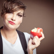 Studio portrait of beautiful young woman with apple in her hand — Stock Photo