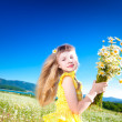 Little beautiful girl holding bouquet of daisies standing in field on blue sky background — Stock Photo