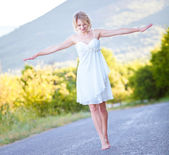 Young slim woman walking barefoot on the road — Stock Photo