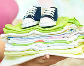 Pregnant woman holding stack of children's clothing — Stock Photo