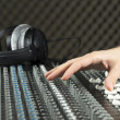 图库照片: Hand on studio mixer