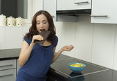 Woman biting chocolate in the kitchen — Stock Photo