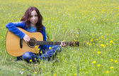 Young woman playing an acoutic guitar in the fields — Stock Photo