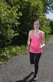 Jovem mulher a sorrir é jogging ao ar livre num dia de verão ensolarado. — Fotografia Stock