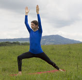 Man in Warrior Pose during yoga outdoors in nature — Stock Photo