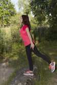 Young jogger woman stretching in nature after sports — Zdjęcie stockowe