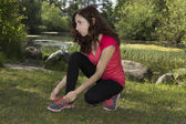 Fitness woman concentrated before sports tying her sports shoes — Stock Photo